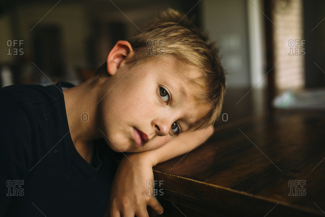 Portrait of serious boy lying head on table at home