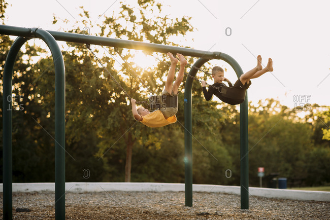 Full length of playful brothers swinging on swings at playground