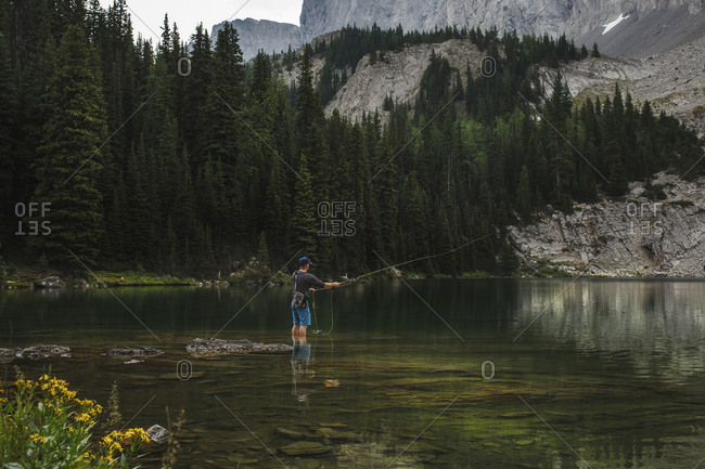 Hiker casting fishing line in lake against mountains at forest