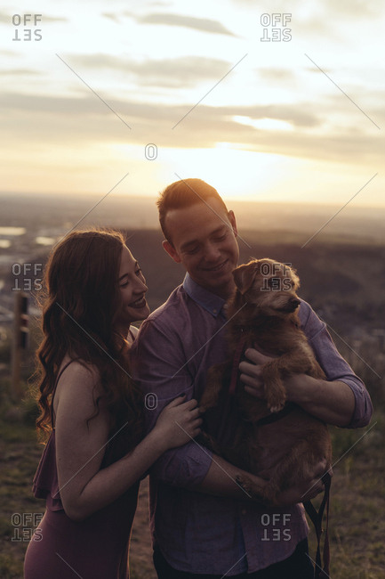 Young couple with dog standing on field during sunset