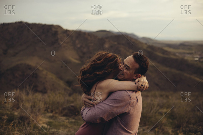 Side view of loving young couple embracing on field against mountains