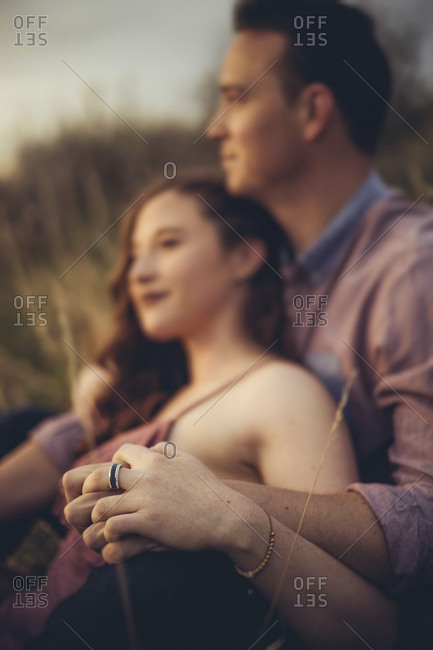 Young couple holding hands while sitting on field during sunset