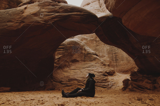 Side view of woman sitting on field by rock formations