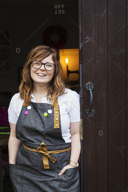 Woman with long brown hair wearing apron and glasses standing in an open doorway, smiling