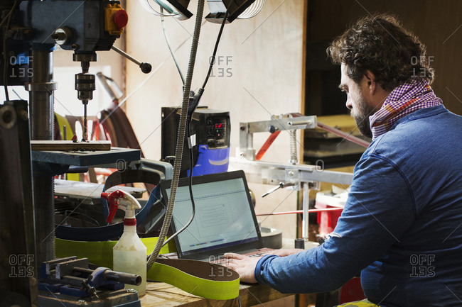 A craftsman at a desk in a workshop using a laptop computer on a cluttered desk
