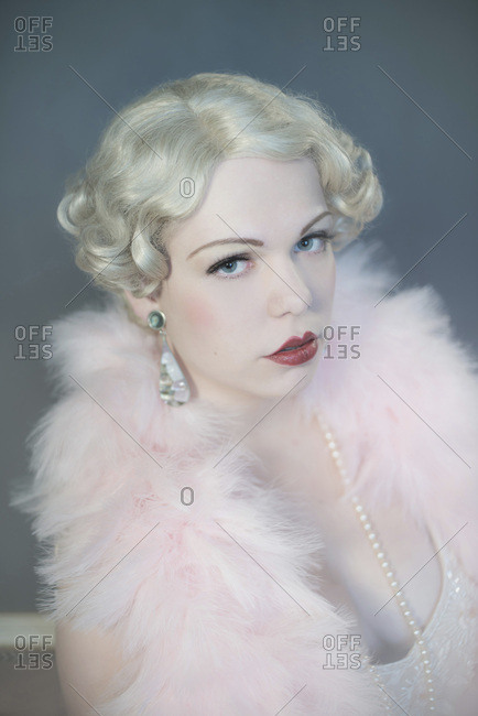 Headshot of vintage 1920s blonde woman in pink feather boa