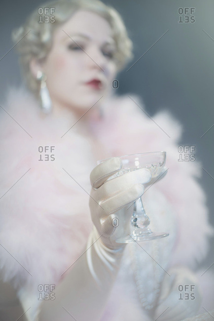 Retro 1920s woman in gloves holding glass of champagne