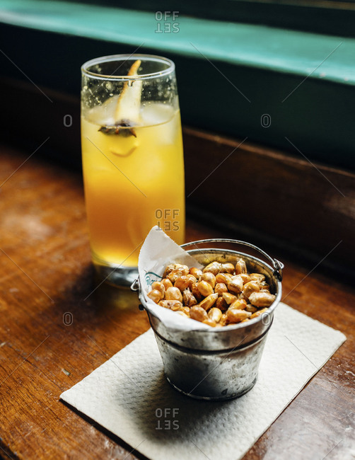Can of toasted corn kernels in front of orange drink on bar top