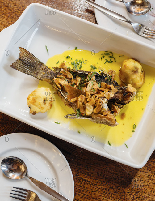 Casserole dish with fried fish in yellow sauce shot from above