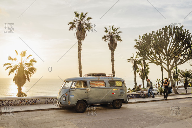 Miraflores, Lima, Peru - November 15, 2017: VW van parked along boardwalk with palms at sunset