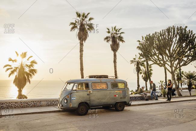 Miraflores, Lima, Peru - November 15, 2017: VW van parked along boardwalk with palms at sunset