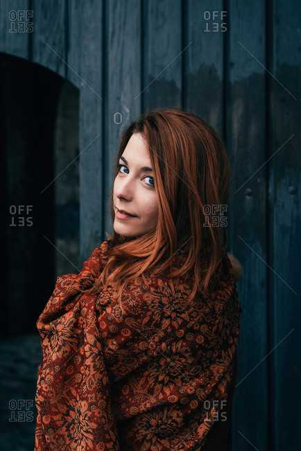 Portrait of ginger girl in front of blue vintage doors wrapped in scarf