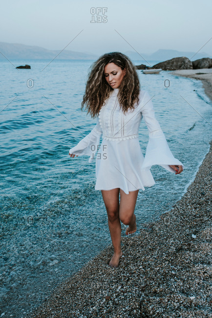 Portrait of girl with long curly hair in white summer dress on the beach at the sea