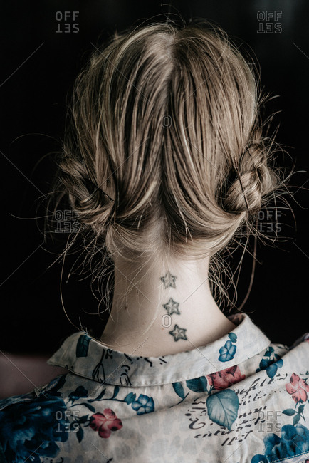Back of the head of girl with retro hairstyle and tattoo on her neck
