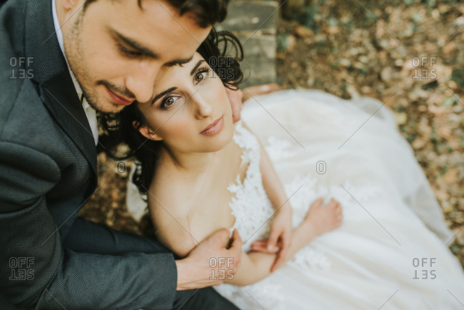 Brunette bride wearing long white wedding dress and groom in the woods looking in love