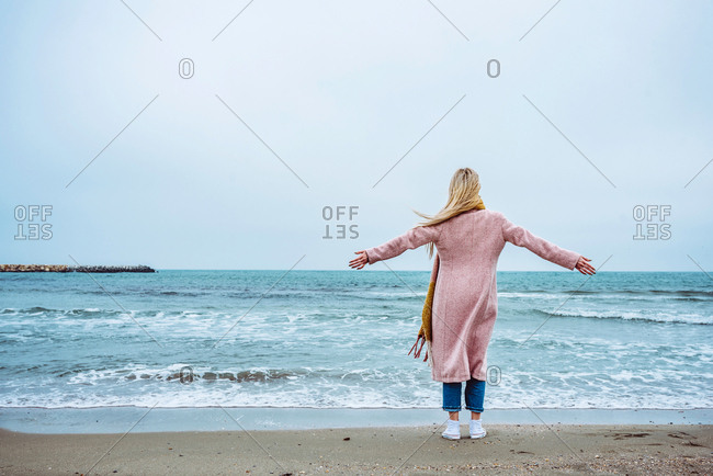 Woman in pink coat standing on the beach facing the sea with arms wide open