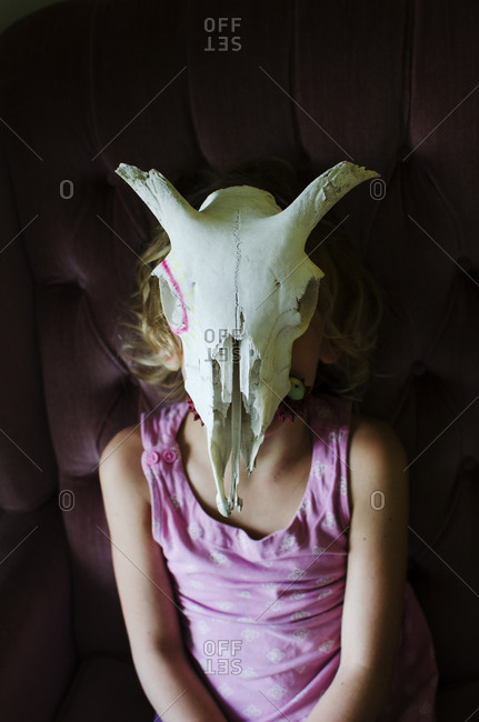 Young girl wearing goat skull as a mask