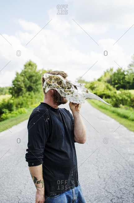 Young man on country road wearing a moose skull as a mask