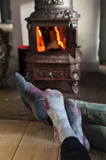 People wearing socks warming their feet near wood-burning stove in cottage