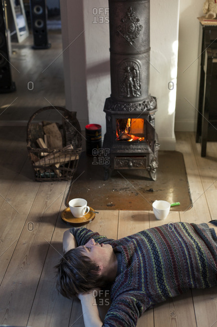 Person lying on floor with hot beverage next to wood-burning stove in cottage