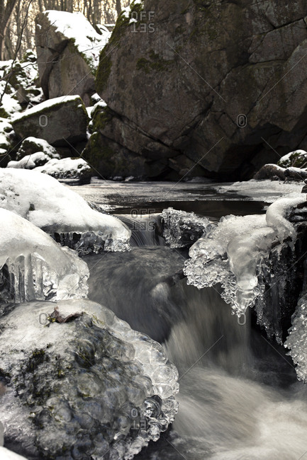 Creek flowing in frozen landscape in nature reserve in Sweden