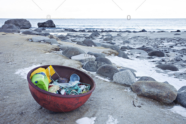 Fishing gear and plastic items in large container on beach in Norway