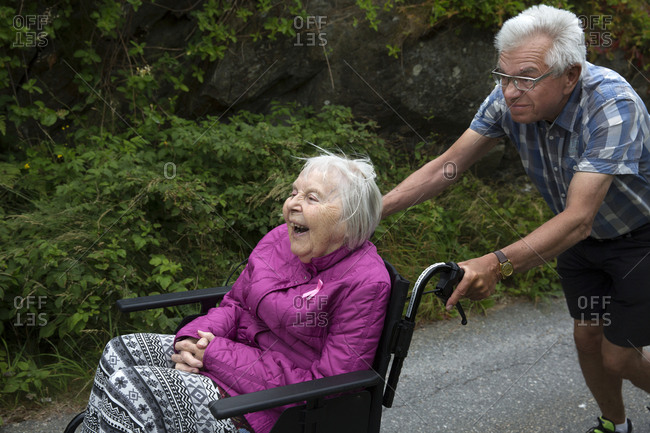 Senior man pushing senior woman on wheelchair