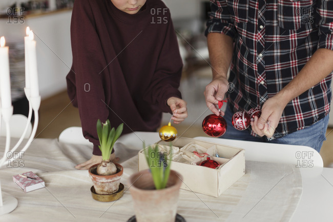 Father and daughter holding Christmas baubles