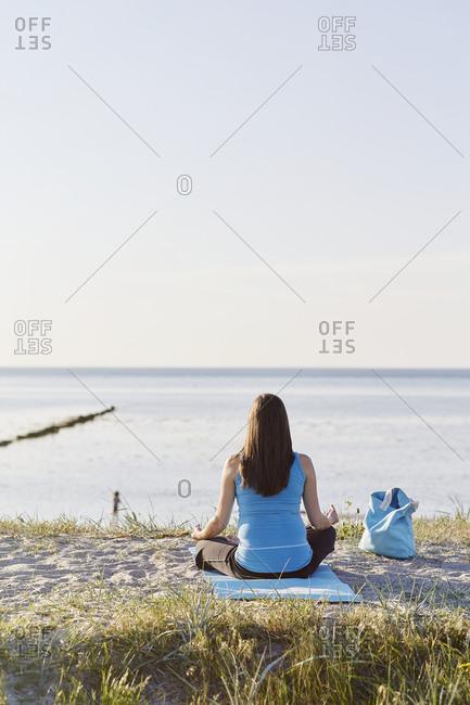 Woman practicing yoga at seaside