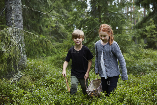 Girl and boy carrying basket in forest