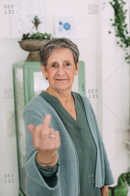 Senior woman showing middle finger