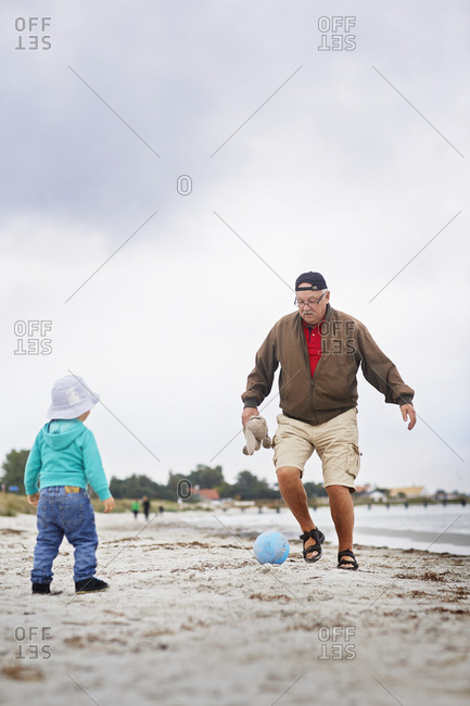 Grandfather kicking ball on beach with grandson