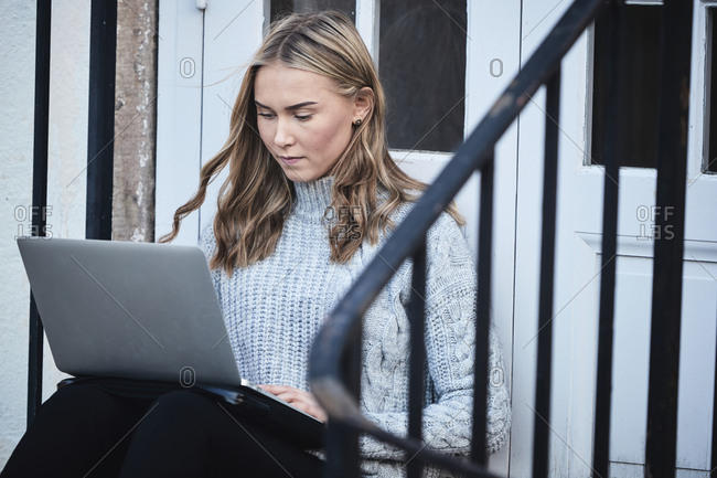 Woman using laptop on front stoop