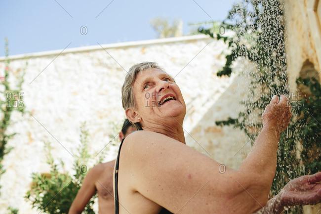 Senior woman taking shower outdoors