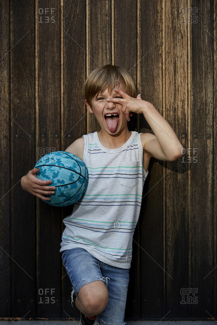 Portrait of boy holding ball and sticking tongue out