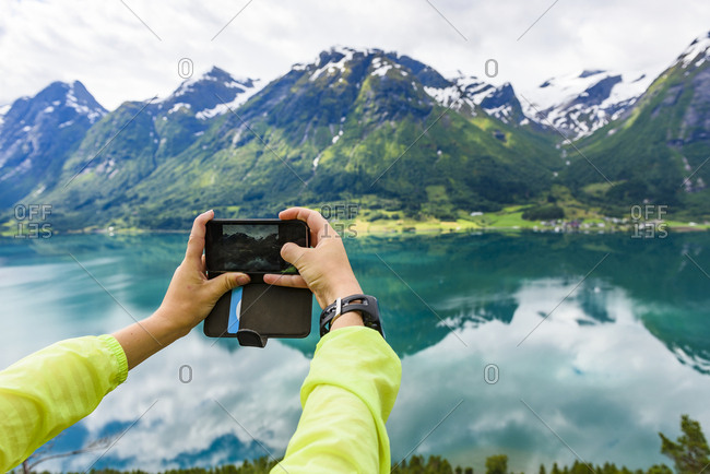 Person photographing mountains and lake