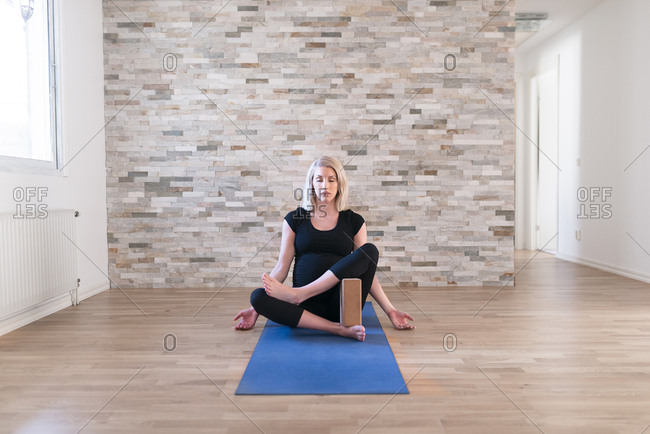 Pregnant woman practicing yoga using yoga block