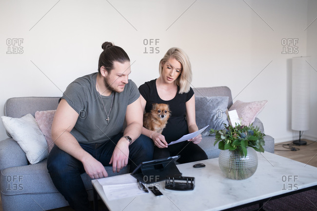 Pregnant woman and partner doing paperwork on couch