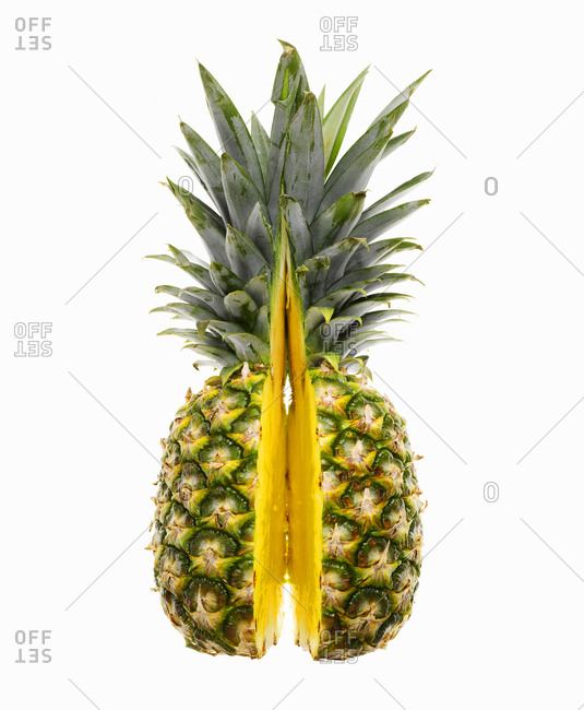 Fresh pineapple sliced in half against white background