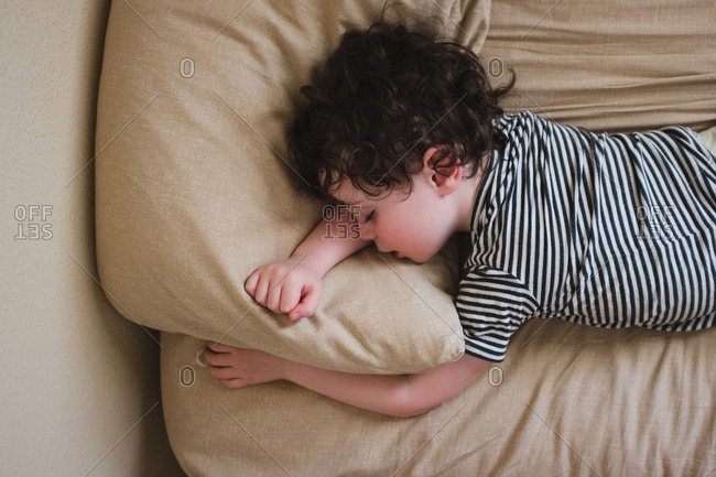 Little boy napping on bed