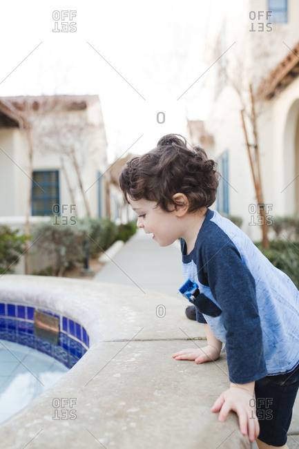 Eager little boy climbing on side of pool