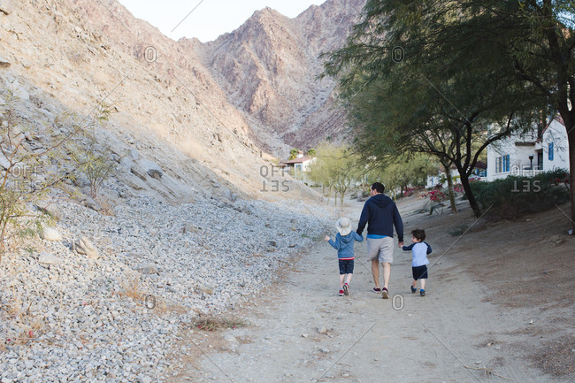 Dad takes his boys for a walk along path leading to arid hills