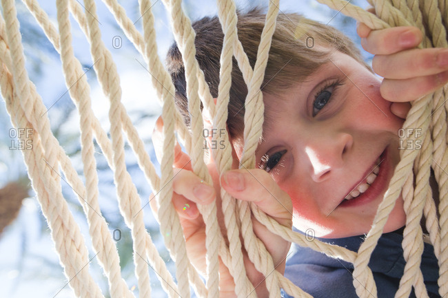 Portrait of young boy looking through strings of hammock