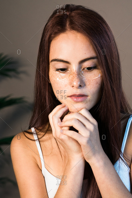 Woman with freckles wearing eye treatment