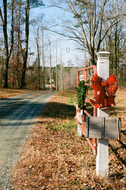 Christmas decorations on gatepost and open gate in rural setting