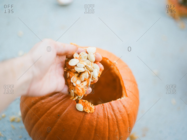 Close up of young boy scooping seeds out of pumpkin