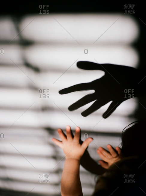 Toddler chasing shadows of parent's hand on wall