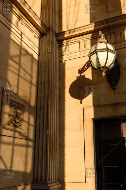 Elegant lamp lit by setting sun outside doorway in Leeds, United Kingdom