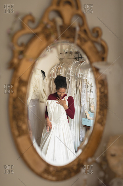 Reflection of bride trying wedding dress from clothes hanger in the mirror at boutique
