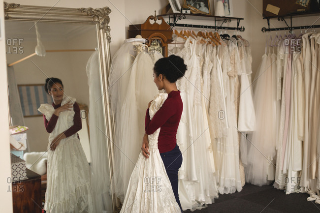 7f7f609f82d Young bride with white dress looking into mirror at boutique stock photo -  OFFSET